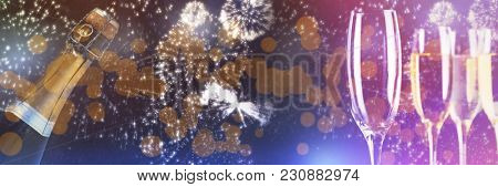 White fireworks exploding on black background against three full glasses of champagne and one empty