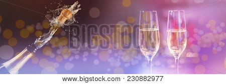 Two glasses of champagne against champagne cork popping