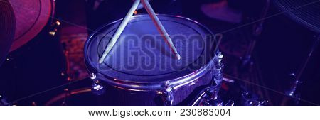 Mid section of drummer performing at concert in nightclub
