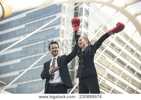 Happy Businesswoman With Boxing Gloves On Arms Raised In Victory Stands With Businessman.concept Fig