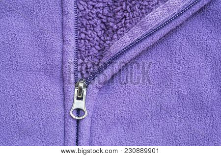 Closeup Head Of Zipper At Purple Jacket Textured Background
