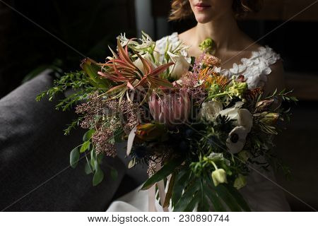 Bride Holds Lush Wedding Bouquet With Different Flowers And A Lot Of Greenery. Wedding Bouquet.