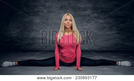 Cute Blonde Female Sits In Legs Spilt Over Grey Background.
