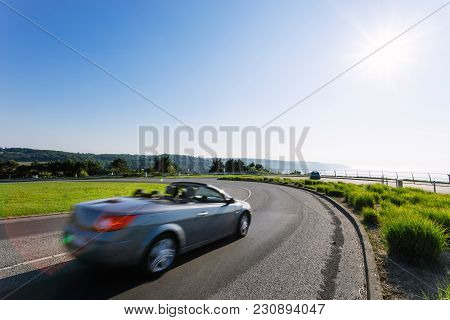 Cars driving on the asphalt curvy road passing through green fields and forests. Countryside landscape on a bright sunny day in France. Industrial agriculture, road network and transportation concept poster