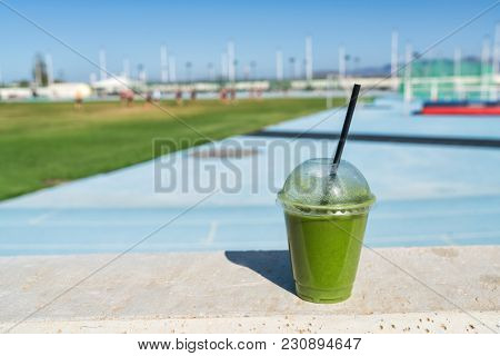 Green smoothie detox juice drink at outdoor sports stadium for runners athletes on blue running track. Healthy diet protein shake for sport people.