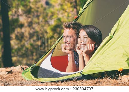 Two young people relaxing in camping tent in summer outdoors nature mountains forest. Happy couple tourists relaxing in sun, travel holidays. Campers outside.