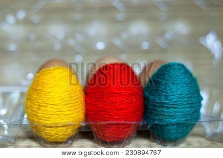 Red, Yellow And Green Eggs In The Plastic Container. Eggs Are Threaded In Colored Thread