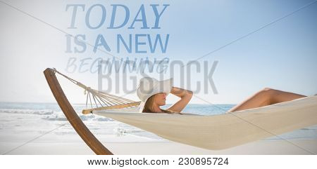 Today is a new beginning against woman wearing sunhat and bikini relaxing on hammock