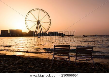 Two Sunbeds With Ain Dubai Ferris Wheel View At Jbr Beach At Sunset