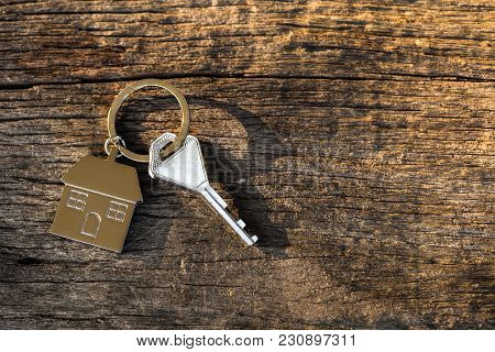 Keychain With House Symbol, Key On Wooden Background. Home Loan Concept.