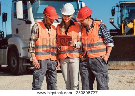 truck drivers and dispatcher in front of lorries in freight forwarding company looking at tablet computer