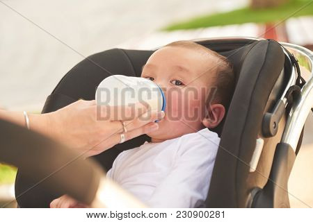 Close-up Image Of Mother Feeding Baby With Formula