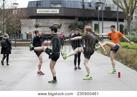 London, England - March 12, 2017 Men In Sports Uniforms Do Exercise On The Street