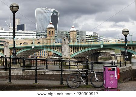 London, England - March 12, 2017 A Bicycle Is Next To A Pink Trash Near The Embankment On The Backgr
