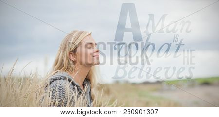A man is what he believes against side view of cute thoughtful woman sitting at beach