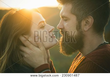 Man With Beard Holds Womans Head With Tenderness, Close Up. Couple With Passionate Faces Stand Close
