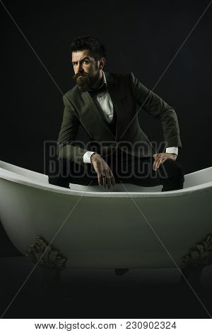 Man With Beard And Mustache On Dark Background. Guy With Strict Face In Luxury Suit Sit In Bathtub.