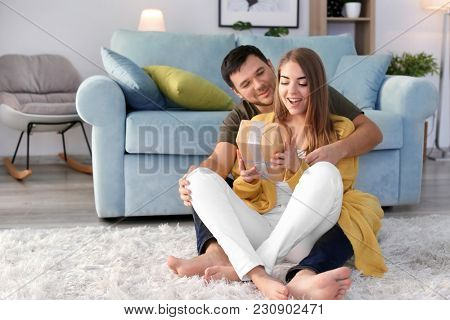 Young woman receiving present from her beloved boyfriend at home