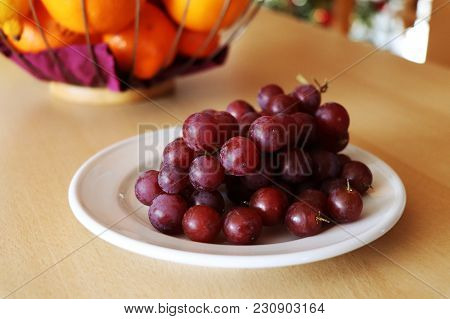 The Red Grapes On The White Plate And In The Background There Are Fruits In The Bowl