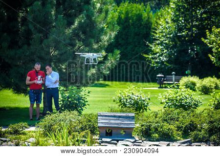 Compact Drone Hovers In Front Of Two Hipster Men. Quad Copter Flies Near Pilot. Farmer And Agronomis