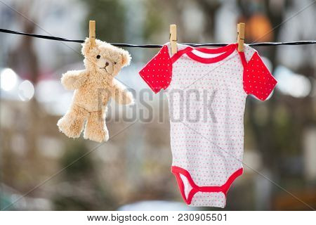 Baby clothes and a teddy bear hanging on the clothesline