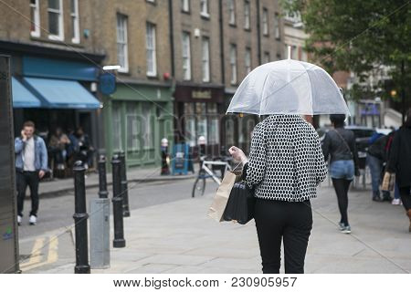 London, England - July 12, 2016 A Girl In A Black And White Plaid Fashion Jacket Under A Transparent