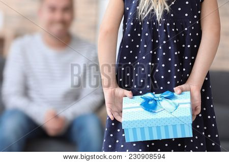 Cute little girl holding gift for father behind her back, closeup