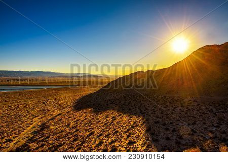 Sunset In Mojave Desert Near Palm Springs With Windmills Farm And Water Reservoirs In The Background