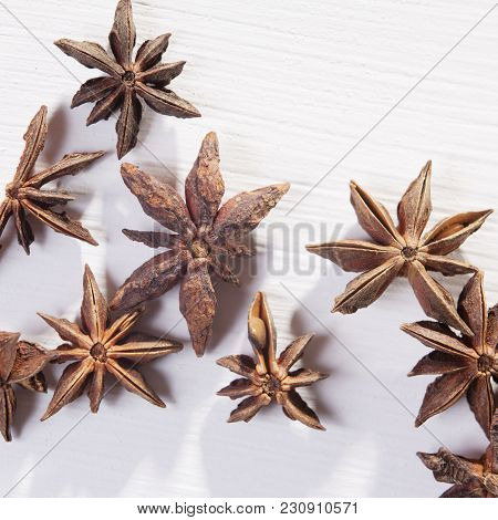 Star Shaped Anise Seeds On A White Wooden Background