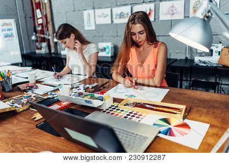 Designers Workspace. Two Female Artists Drawing Decorative Elements Sitting At Desk In Creative Stud