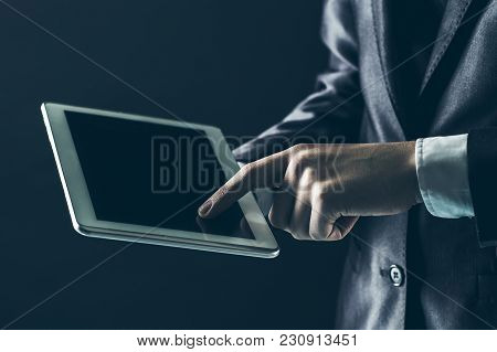 Businessman Finger Presses On Screen Digital Tablet.photo On A Black Background And Has Space For Yo
