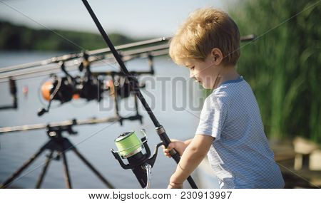 Little Boy Learn To Catch Fish In Lake Or River. Child With Fishing Rod On Sunny Day. Childhood, Edu