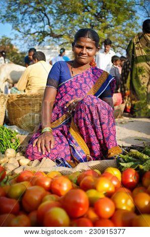 KAMALAPURAM, INDIA - FEBRUARY 2, 2015: Female street vendor selling her produce at vegetable stand.