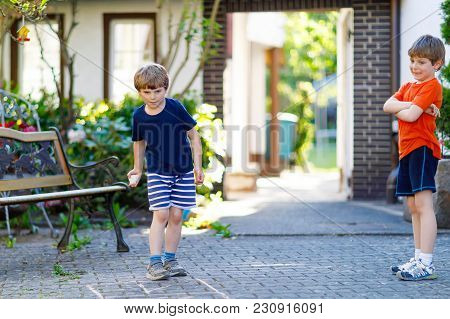 Two Little School And Preschool Kids Boys Playing Hopscotch On Playground Outdoors Together. Childre