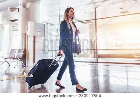 Elegant Young Woman Walking And Pulling Her Suitcase In The Airport Terminal.