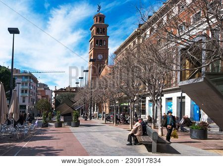 HOSPITALET DE LLOBREGAT, SPAIN - MARCH 9, 2018: A view of the Ajuntament square, the main square in the Hospitalet Centre district, highlighting the belfry of the Saint Eulalia of Merida on the right