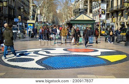 BARCELONA, SPAIN - FEBRUARY 23, 2018: People stepping on the Pla del Os mosaic in the popular La Rambla. Thousands of people walk daily on the mosaic, designed by famous Catalan artist Joan Miro
