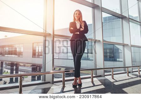 Full-length Portrait Of Attractive Model With Fair Hair Wearing Elegant Formal Suit Standing With Ar