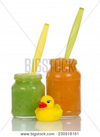 Baby Food, Fruit Purees In Jars Next Toy Duck Isolated On White Background