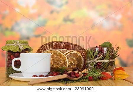 Jars With Rose Hips, Basket Of Dry Citrus Slices, Spoon And Cup With Saucer, On Wooden Table