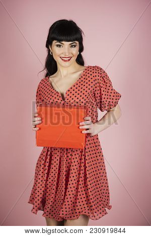 Femininity And Attraction Concept. Attractive Woman With Makeup Holds Red Box Or Gift On Pink Backgr