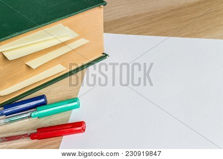 White Sheet Of Paper And Big Green Book With Marked Pages And Color Pencils