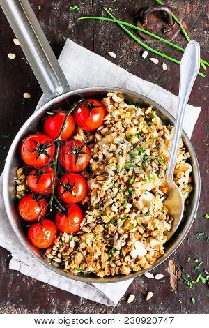 Savory Crumble With White Fish Cod And Mixed Seeds Served With Roasted Cherry Tomatoes In A Pan On A