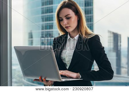 Young Female Lawyer Working In Her Luxurious Office Holding A Laptop Standing Against Panoramic Wind