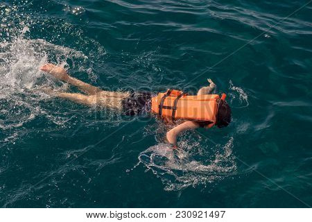 Woman Snorkeling Over Coral Reef In Blue Sea