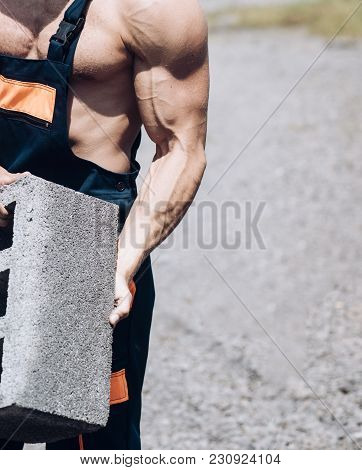 Muscles And Power Concept. Work At Construction Site. Torso Of Male Muscular Builder In Overalls. Se
