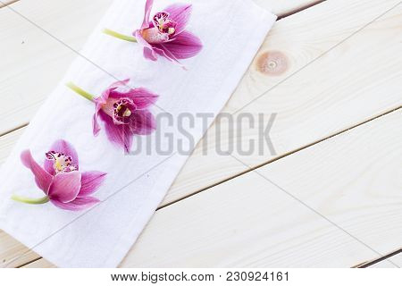 Spa And Wellness Setting With Orchid, Towel On Wooden White Background Closeup