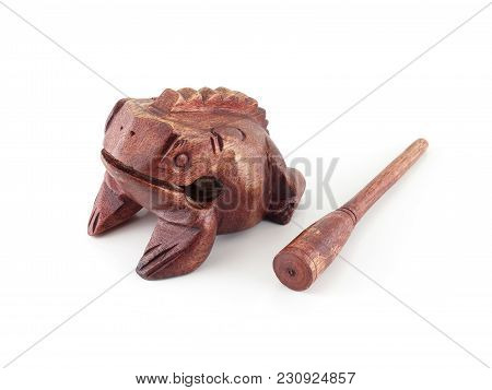 close-up brown wooden frog carved with scraper stick isolated on white background, thai percussion musical instrument sounds like a frog for rhythmic accompaniment, gift souvenirs about fortune belief