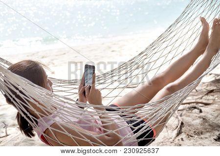 Woman Using Mobile Phone On Cozy Mesh Hammock At Beach.