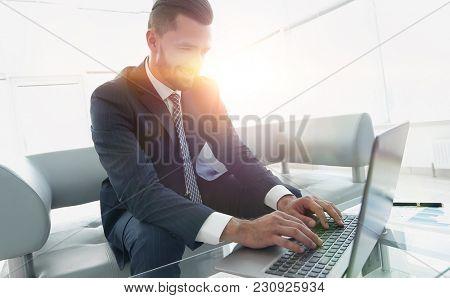 Smiling businessman browsing information on laptop,